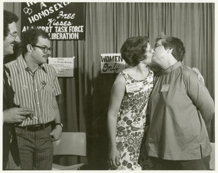 Barbara Gittings and Isabel Miller kissing at the Hug a Homosexual booth, ALA - Kay Tobin Lahusen, 1971